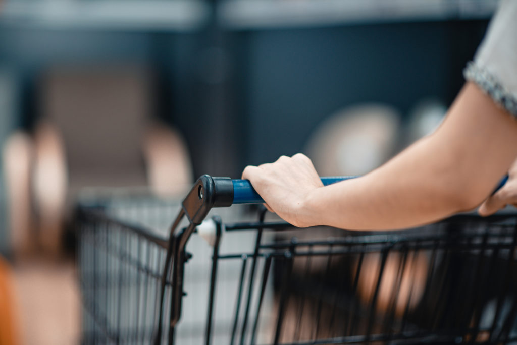 Person holding grocery cart handle.